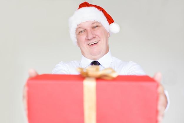 Joyful business man in santa hat giving gift