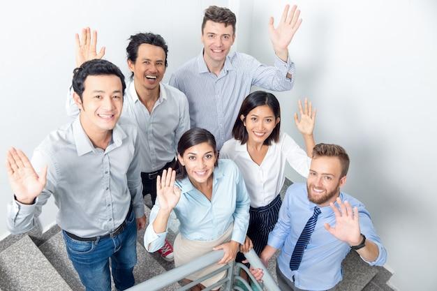 Joyful business team waving on office stairway