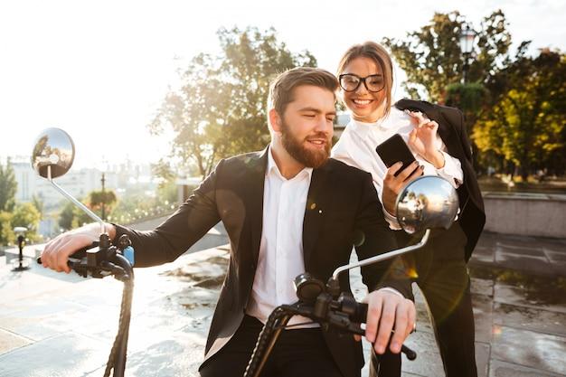 Joyful business woman standing near bearded man in suit