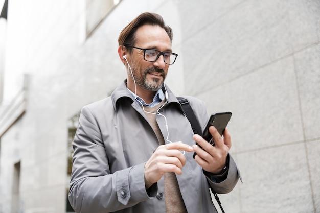 Радостный бизнесмен в очках с помощью мобильного телефона и наушников, стоя возле офисного здания
