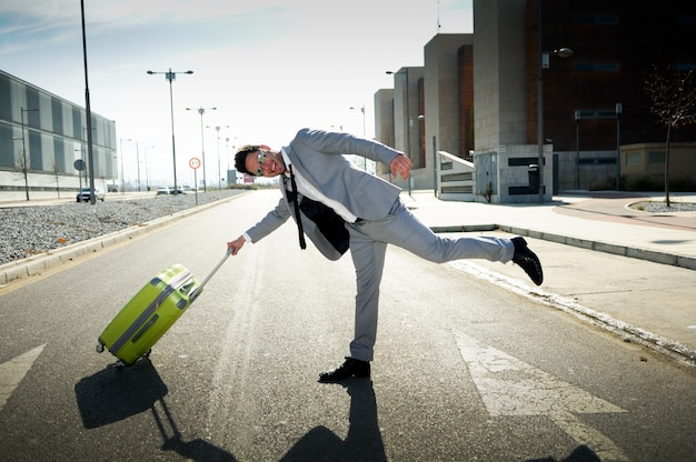 Joyful businessman playing with his suitcase