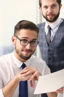 Радостные бизнесмены, работающие с документами в офисе