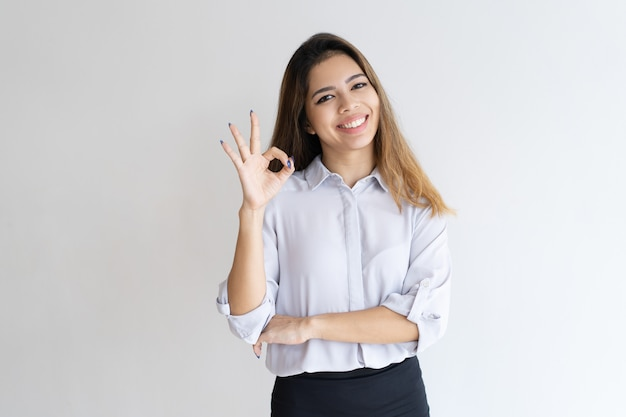 Joyful businesswoman gesturing ok