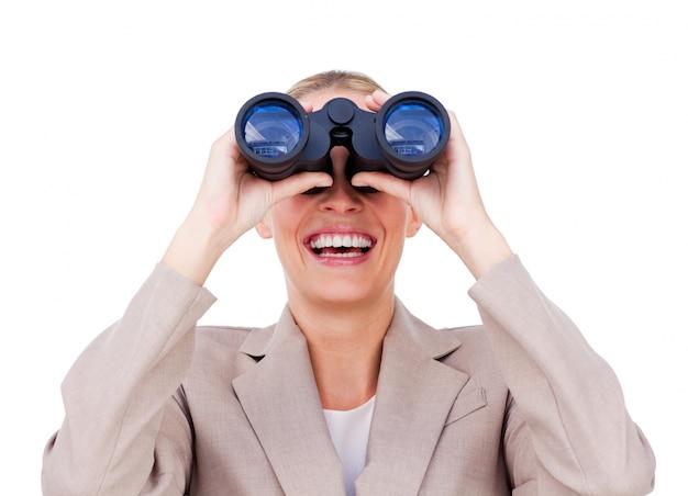 Joyful businesswoman predicting future success through binoculars