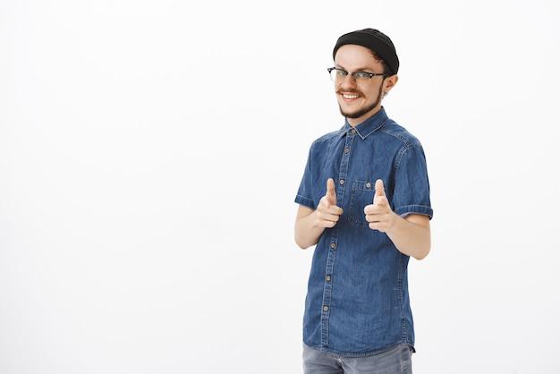 Радостный беззаботный и расслабленный стильный красавец с бородой в очках и черной шапке, указывающий жестом пальца, широко улыбаясь, приветствуя товарищей