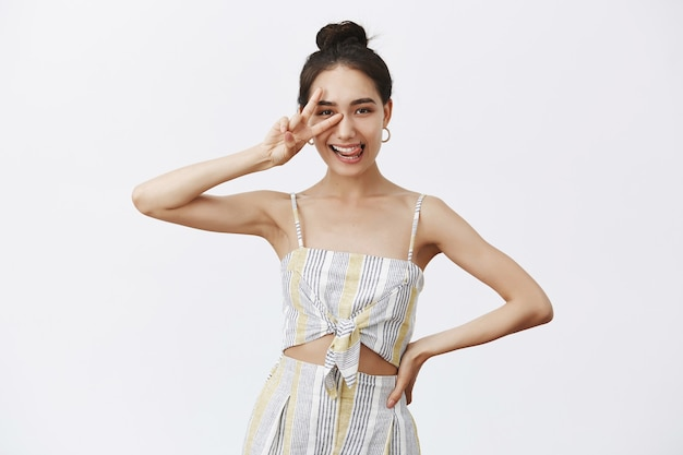Joyful and carefree creative female designer in elegant outfit and bun hairstyle, showing peace or victory sign over eye, sticking out tongue playfully, holding hand on waist