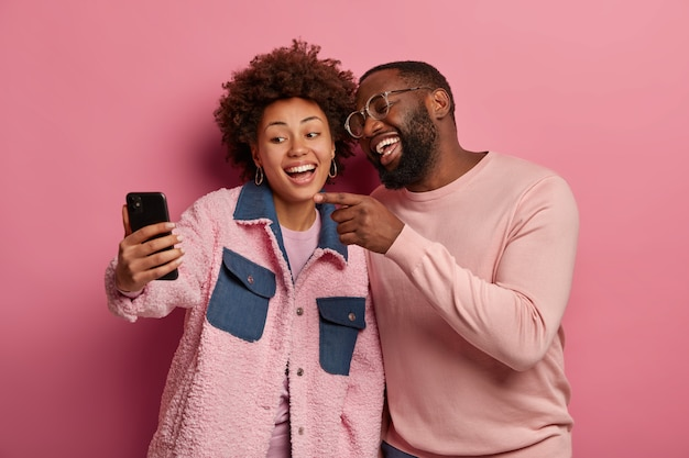 Joyful carefree dark skinned millennial couple take selfie on modern cellphone, man points at display with happy laugh, make photo of themselves