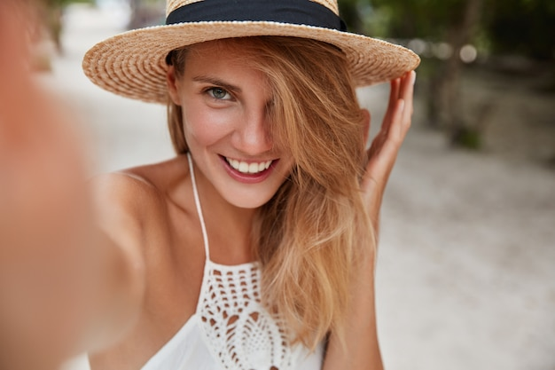 Joyful carefree female wears fashionable straw summer hat on modern device and makes selfie, strolls outside during sunny summer weather. people, lifestyle and rest concept.