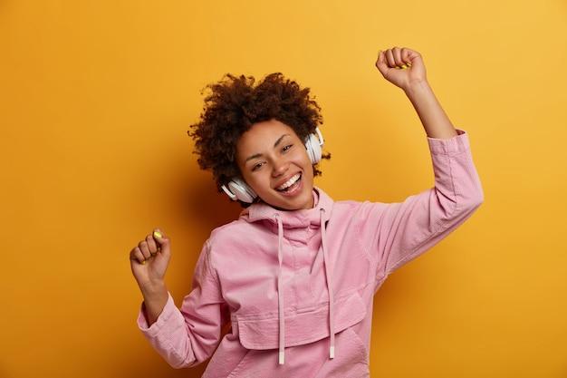 うれしそうなのんきな女性は音楽に合わせて踊り、お気に入りのオーディオトラックを聴き、くいしばられた握りこぶしで手を上げ、広く笑顔で、黄色い壁に隔離されたバラ色のスウェットシャツを着ています。人、レジャー、エンターテインメント