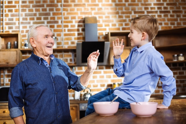 Радостный заботливый пожилой мужчина веселится со своим внуком, стоя на кухне