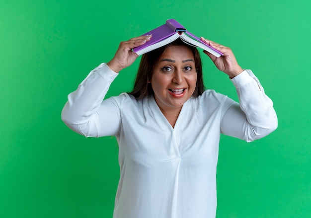 うれしそうなカジュアルな白人の中年女性が本で頭を覆った