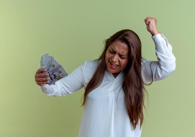 Donna di mezza età caucasica casuale gioiosa che tiene soldi e pugno di sollevamento