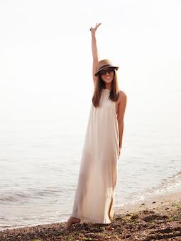 Радостная случайная девушка гуляет на морском пляже и счастлива улыбается
