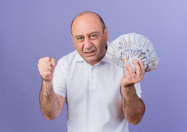 お金を保持し、紫色の背景で隔離のイエスジェスチャーを握りこぶし