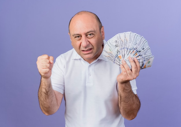 Gioioso imprenditore maturo casual tenendo i soldi e pugno di serraggio facendo sì gesto isolato su sfondo viola