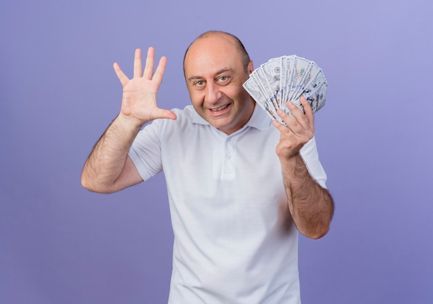 Joyful casual mature businessman holding money and showing five with hand isolated on purple background with copy space