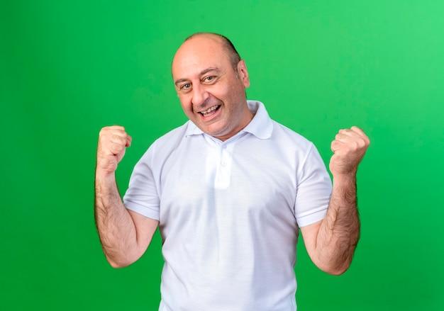 Радостный случайный зрелый мужчина показывает жест да, изолированный на зеленой стене