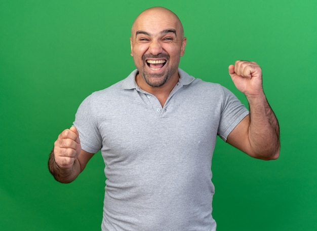 Joyful casual middle-aged man doing yes gesture isolated on green wall