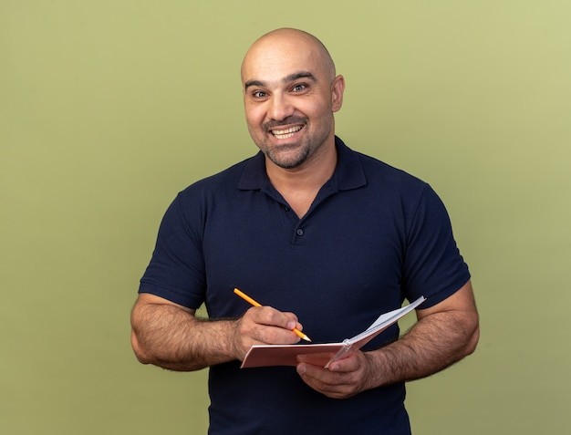 Joyful casual middle-aged man holding pencil and note pad isolated on olive green wall