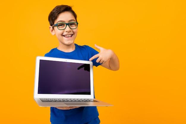 즐거운 백인 소년 복사 공간 노란색 스튜디오 배경에 최대 조롱 노트북 화면을 보유하고