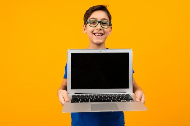 즐거운 백인 소년 복사 공간 노란색 스튜디오 배경에 모형 노트북 화면을 보여줍니다