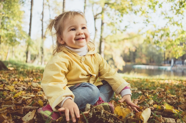 Joyful caucasian child girl in autumn sits on leaves in the park.