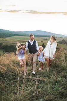 山の田舎フィールドで夏の散歩を楽しんでいる2人の子供とうれしそうな白人家族