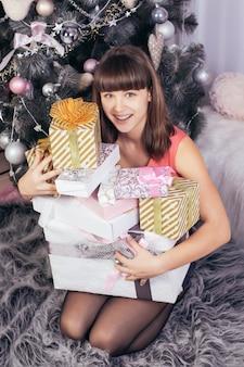 즐거운 백인 소녀는 흰색 포장에 크리스마스 선물 산을 안아