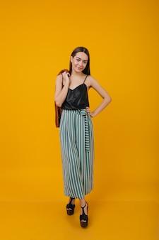 Радостная кавказская девушка позирует в туфлях на высоких каблуках. портрет удивительной девушки-модели в шелковой черной майке.