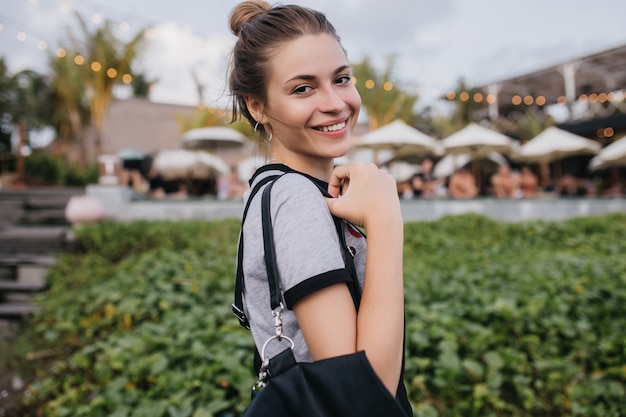 笑顔でポーズをとるカジュアルな髪型のうれしそうな白人の女の子。自然を笑っている魅力的な黒髪の女性の屋外写真。