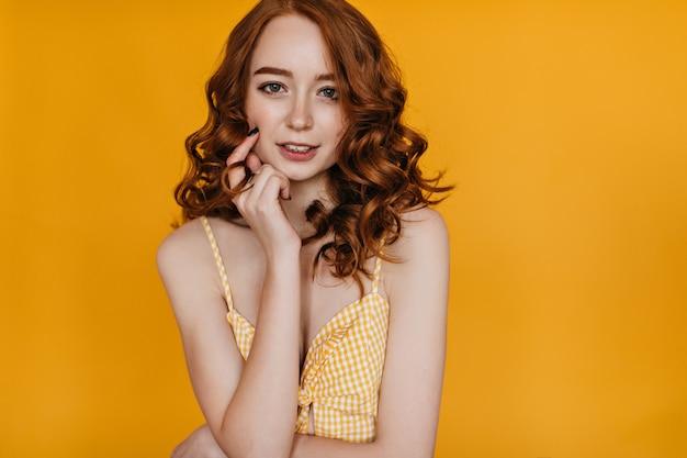 生姜髪のうれしそうな白人の女の子が笑顔で彼女の顔に触れています。黄色い服装の壮大な若い女性モデルの屋内写真。