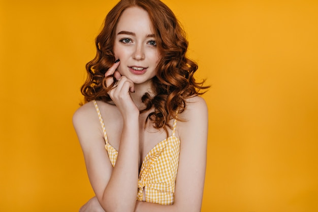 Joyful caucasian girl with ginger hair touching her face with smile. indoor photo of spectacular young female model in yellow attire.
