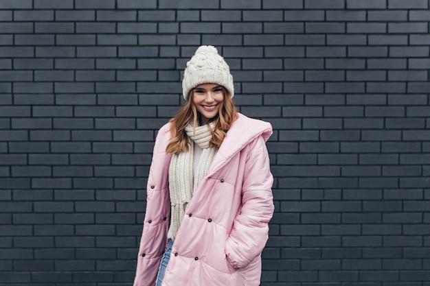 Радостная кавказская дама носит розовое пальто и развлекается в холодный день. наружное фото веселой девушки, стоящей возле кирпичной стены и улыбающейся.