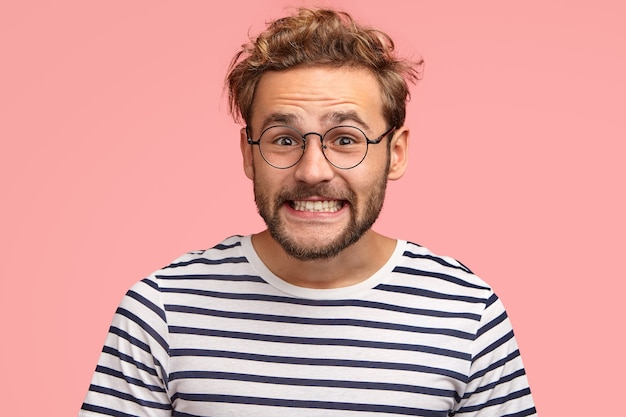 Joyful caucasian male clenches teeth and looks positively, has curly hair, wears spectacles and striped sweater, isolated over pink wall. happy man freelancer rejoices success