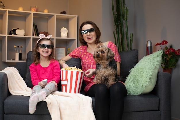 うれしそうな白人女性とソファの上に座ってテレビでコメディ映画を見て3dメガネをかけた彼女の小さな娘は、ポップコーンを食べて笑っています。