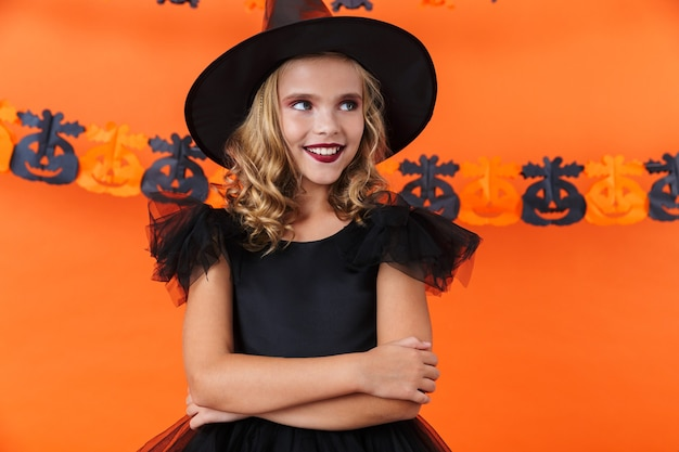 Joyful caucasian woman in black halloween costume smiling and looking aside isolated over orange pumpkin wall