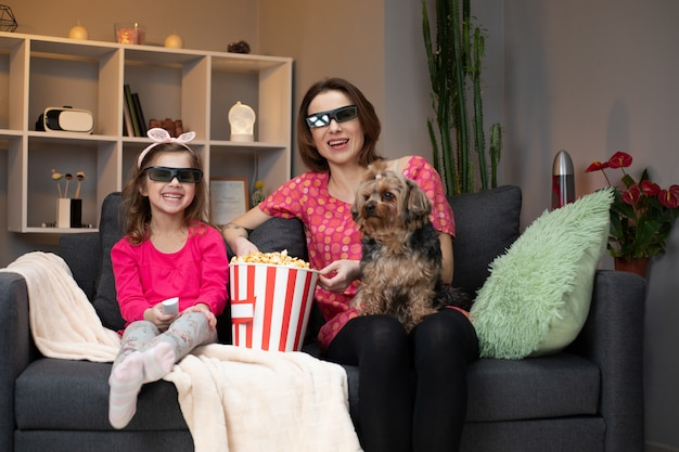 Joyful caucasian woman and her little daughter in 3d glasses sitting on the sofa and watching comedy film on tv while eating popcorn and laughing.