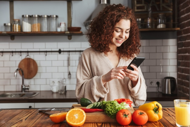 Joyful caucasian woman holding smartphone while cooking salad with fresh vegetables in kitchen interior at home