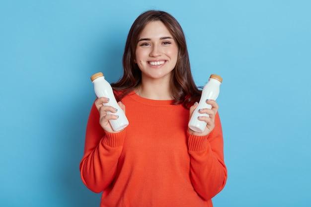 うれしそうな白人女性は2本の牛乳を保持しています
