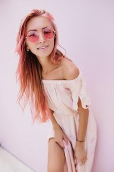Joyful caucasian woman in summer glasses posing near white wall.