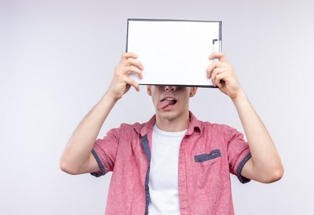 Gioioso giovane caucasico che indossa la camicia rosa ha coperto gli occhi con appunti e mostrando la lingua sul muro bianco isolato