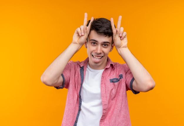 ピンクのシャツを着て両手で平和のジェスチャーをし、孤立したオレンジ色の壁に舌を示すうれしそうな白人の若い男