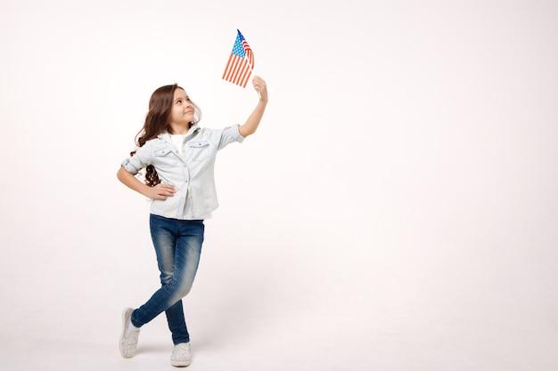 Радостная харизматичная милая девушка держит американский флаг, выражая позитив и стоя изолированной в белой стене