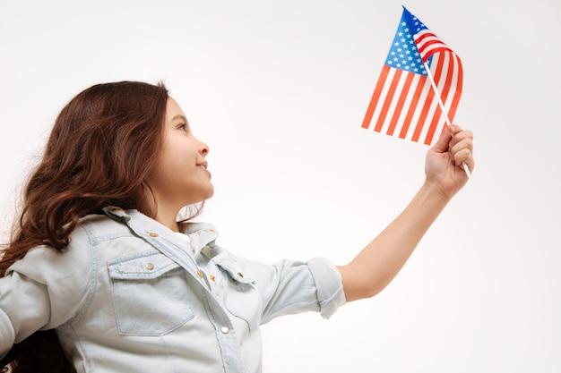 Радостная очаровательная милая девушка держит американский флаг, выражая положительные эмоции и стоя изолированной в белой стене