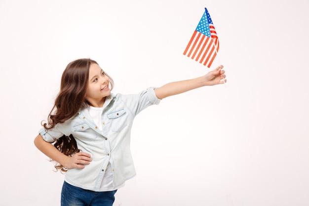 Радостная очаровательная милая девушка держит американский флаг, выражая позитив и стоя изолированной в белой стене