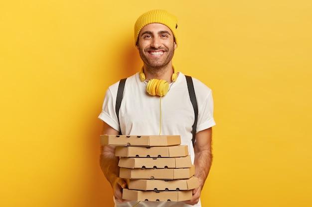 Uomo allegro e allegro in abbigliamento casual, tiene una pila di scatole di cartone con la pizza, ha un'espressione amichevole, usa le cuffie per ascoltare la traccia audio, offre cibo spazzatura, dimostra un buon servizio