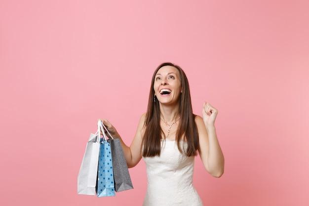 買い物の後に購入した色とりどりのパッケージバッグを見上げて保持している白いドレスを着たうれしそうな陽気な女性