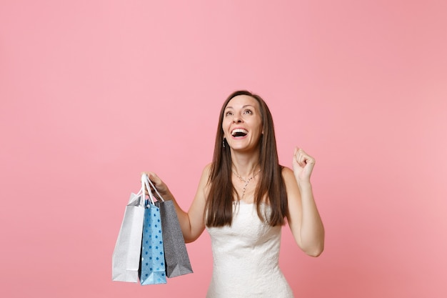 Joyful cheerful woman in white dress looking up and holding multi colored packages bags with purchases after shopping