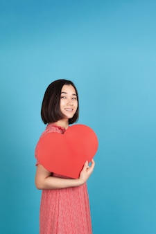 Joyful, cheerful young asian woman in red dress holding big red paper heart like fan