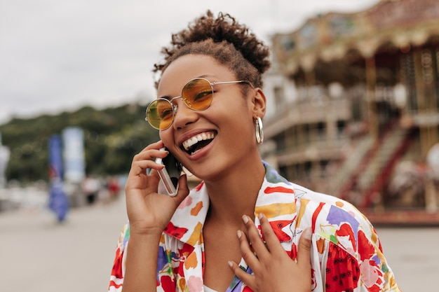 Joyful cheerful young brunette curly woman in colorful shirt and orange sunglasses laughs and talks on phone outside